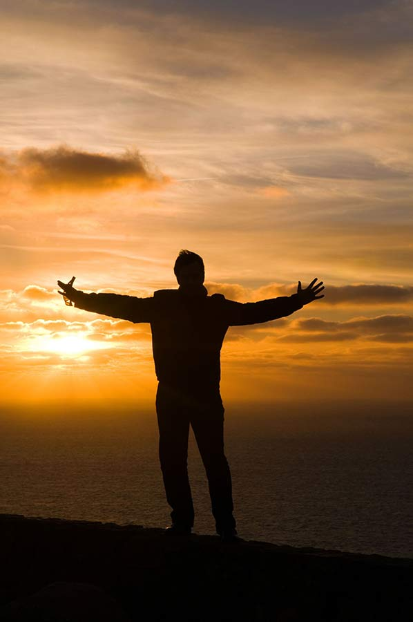 Man silhouette with open hands during sunset