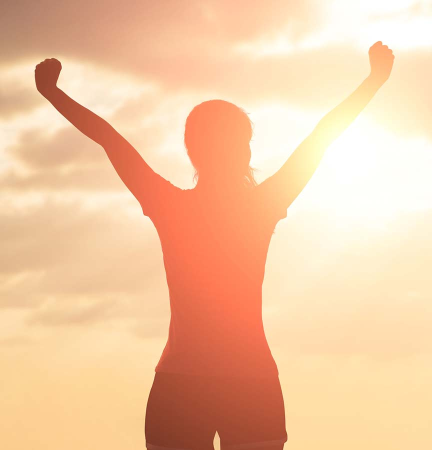 Triumphant person facing sun